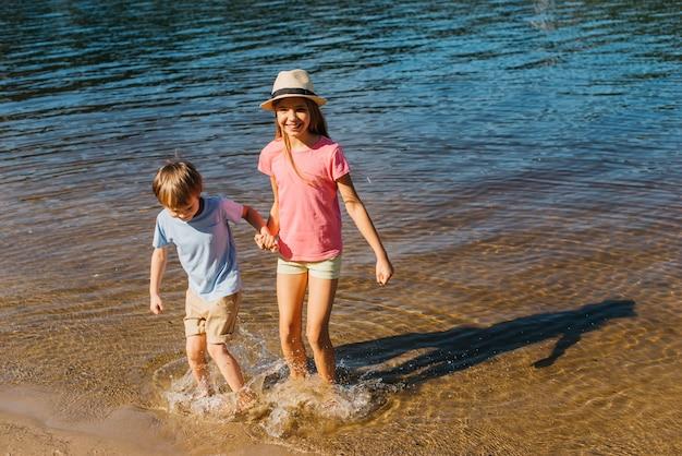 Kinder, die im wasser am strand spritzen
