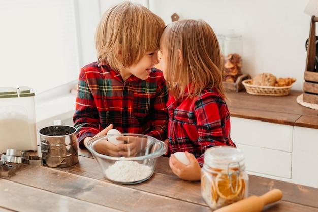 Kinder, die in der küche am weihnachtstag kochen