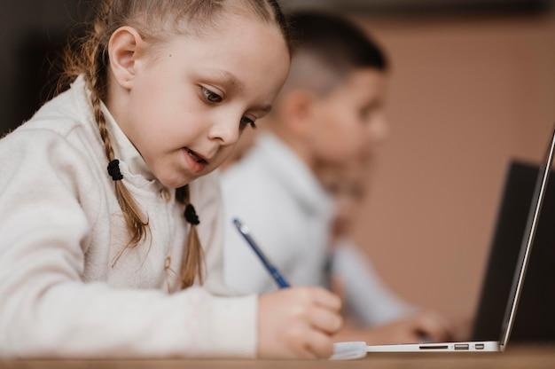 Kinder, die in der schule laptops benutzen