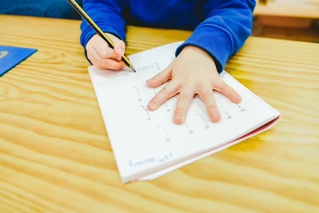 Kinder, die in einer montessori-schule das schreiben lernen.
