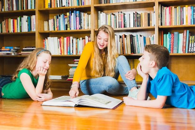 Kinder, die interessantes buch in der bibliothek studieren