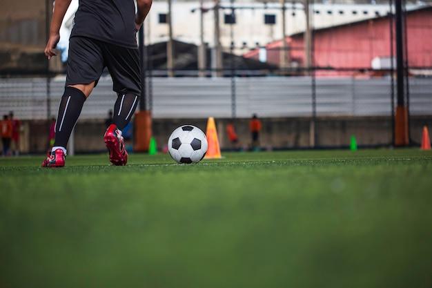 Kinder, die kontrollfußball-taktikkegel auf rasenplatz mit für trainingshintergrund spielen, der kinder im fußball ausbildet