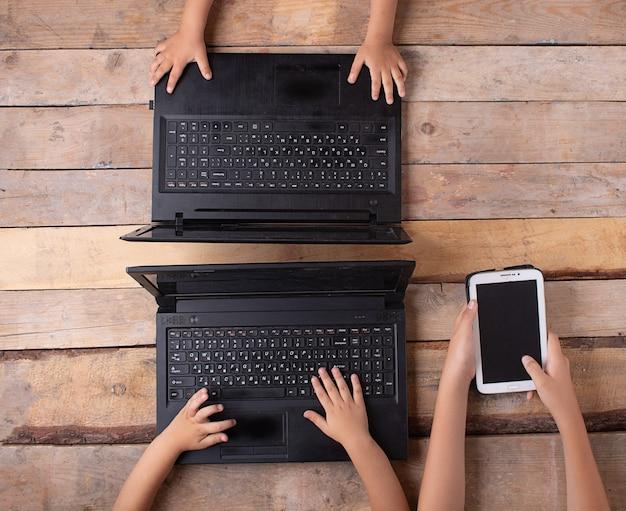 Kinder, die laptop und tablette halten