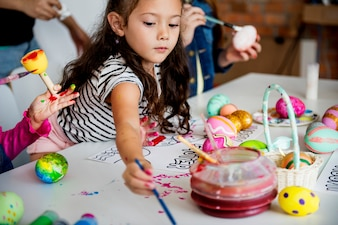 Kinder, die Malereieier Ostern-Feiertag färben