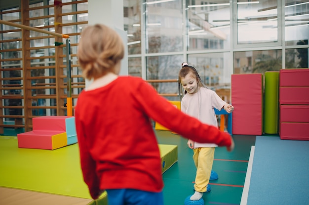 Kinder, die massage-igel für fußbeinübungen im fitnessstudio im kindergarten oder in der grundschule machen. kindersport- und fitnesskonzept.