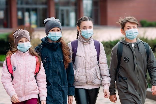 Kinder, die medizinische masken tragen, verlassen die schule.