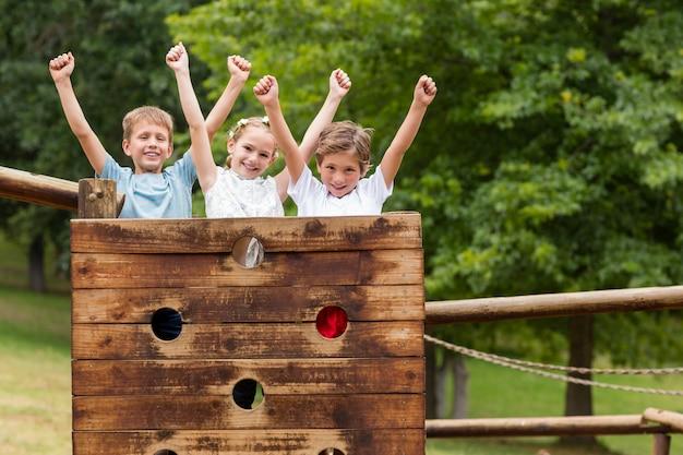 Kinder, die mit den armen oben auf einer spielplatzfahrt im park stehen