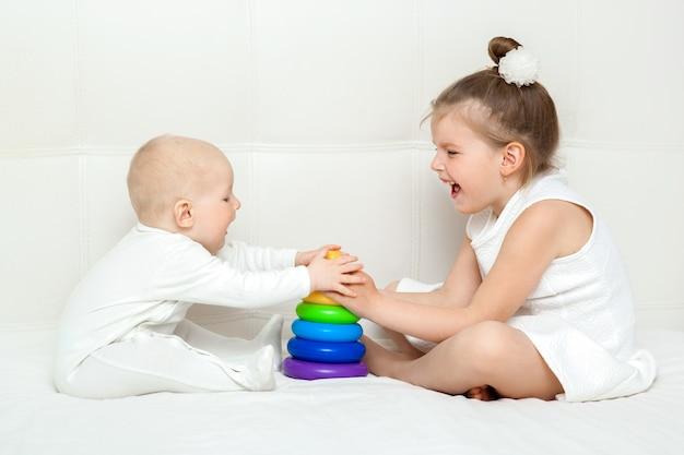 Kinder, die mit der pyramide getrennt auf weiß spielen