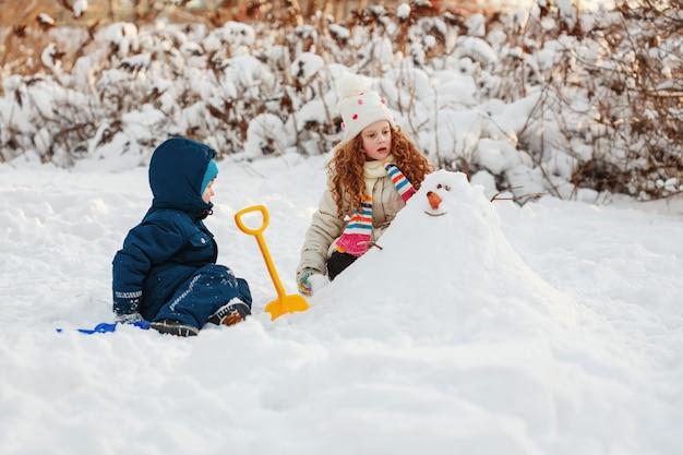 Kinder, die mit einem schneemann auf einem winterweg im park spielen.