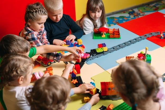 Kinder, die mit erbauerblöcken an der klasse spielen