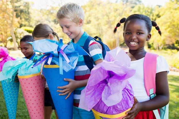 Kinder, die mit ihrer geschenküberraschung während eines sonnigen tages aufwerfen