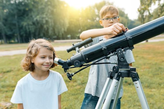Kinder, die mit interesse an einem teleskop zum himmel schauen