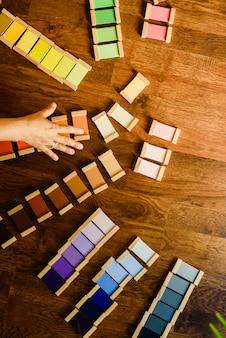 Kinder, die mit Montessori-Farbtabletten spielen und lernen