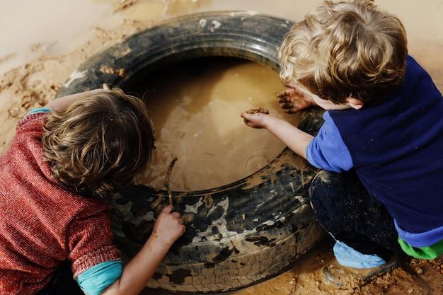 Kinder, die mit schlamm und schmutzigem wasser im wald spaß in den schlammpfützen spielend spielen