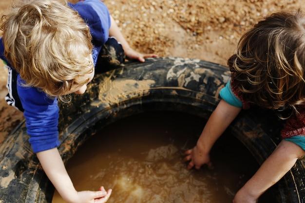 Kinder, die mit schlamm und schmutzigem wasser im wald spielen