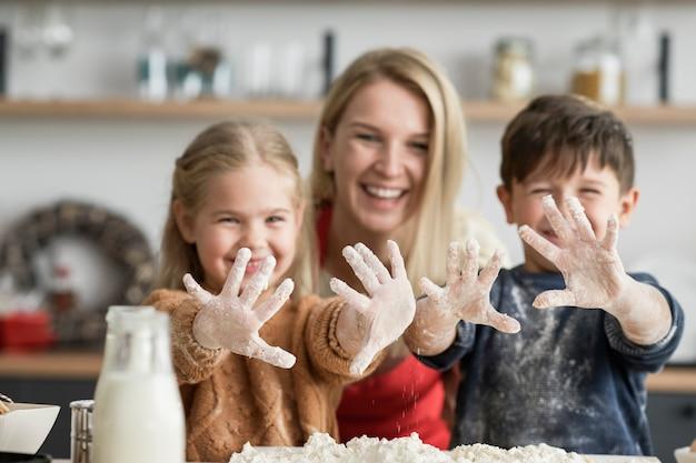 Kinder, die nach dem backen schmutzige hände zeigen