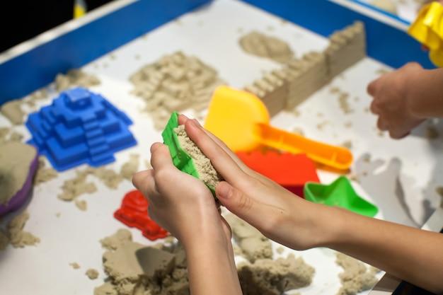 Kinder, die plastikformspielwaren mit sand auf sandkasten spielen.