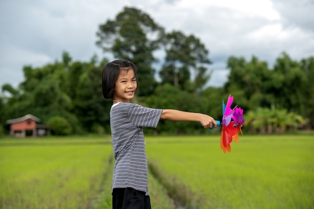 Kinder, die regenbogen-windrad oder windmühle auf blauem himmel und wolkenhintergrund der schönen natur spielen