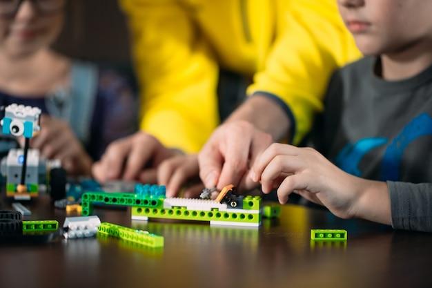 Kinder, die roboter mit lehrer herstellen. frühe entwicklung, diy, innovation, moderne technologie.