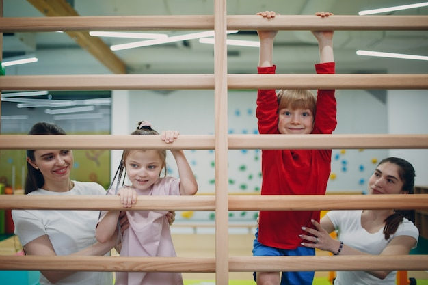 Kinder, die schwedische wandübungen im fitnessstudio im kindergarten- oder grundschulkinder-sport- und fitnesskonzept machen
