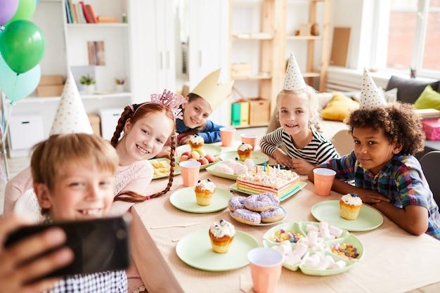 Kinder, die selfie an der geburtstagsfeier nehmen