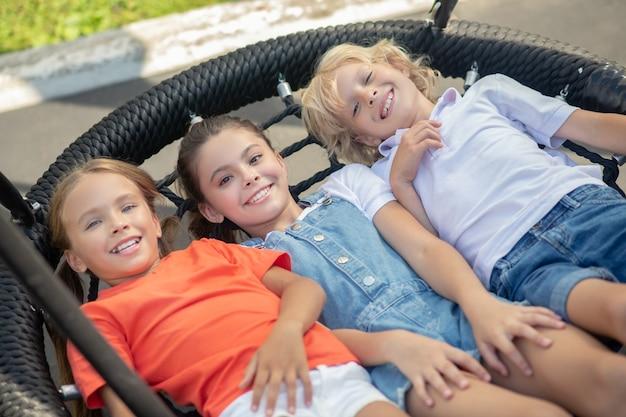 Kinder, die sich nach dem spiel ausruhen und glücklich aussehen