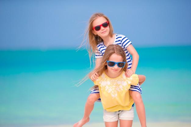 Kinder, die spaß am tropischen strand während der sommerferien zusammen spielen am seichten wasser haben