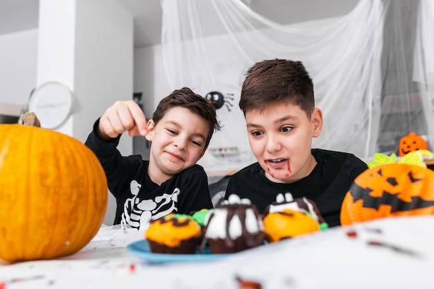 Kinder, die spaß für halloween haben, umgeben mit gruseliger dekoration. jack o 'lantern halloween kürbis und cupcakes auf dem tisch. fröhliches halloween!