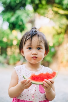 Kinder, die spaß haben und die heißen sommerferien feiern, indem sie wassermelone essen