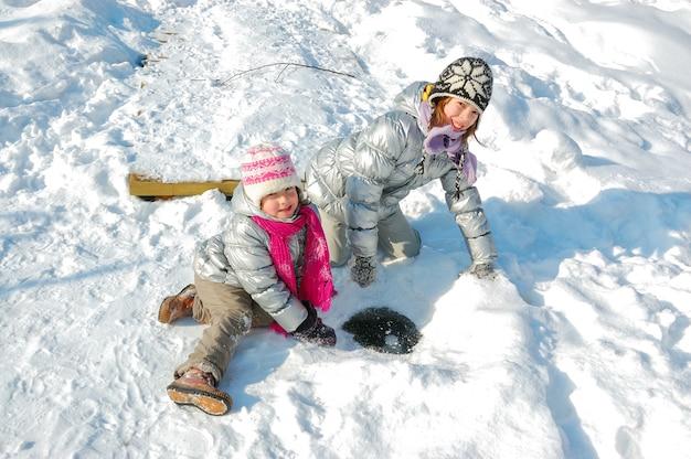 Kinder, die spaß im winter draußen haben, kinder, die mit schnee spielen