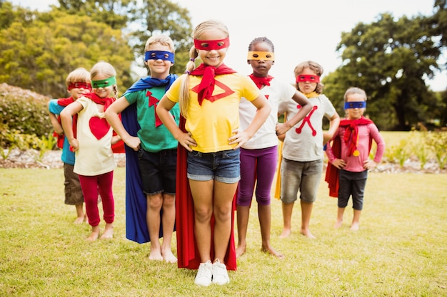 Kinder, die superheldkostümstellung tragen