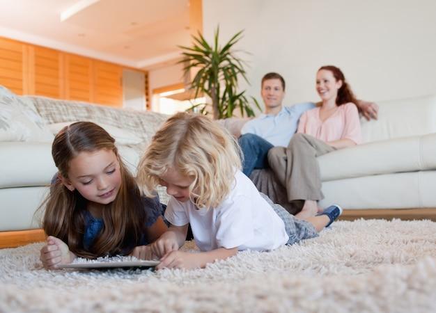 Kinder, die tablette auf dem teppich verwenden