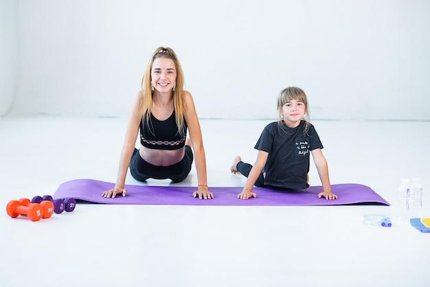 Kinder, die üben, machen mit dem lehrer gymnastik und yoga