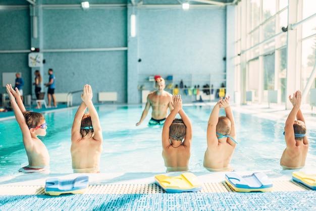 Kinder, die übung im schwimmbad machen