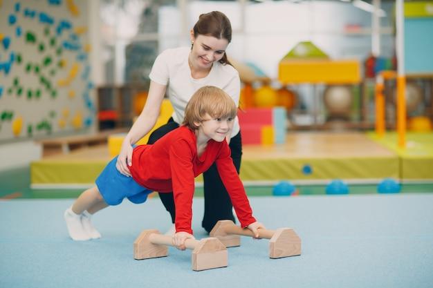 Kinder, die übungen machen, drücken in der turnhalle im kindergarten oder in der grundschule nach oben. kindersport- und fitnesskonzept.