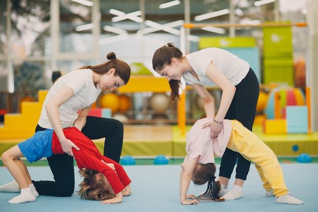 Kinder, die übungsbrücke in der turnhalle im kindergarten oder in der grundschule tun. kindersport- und fitnesskonzept.