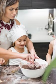 Kinder, die vor mutter beim mischen des kakaopulvers in der schüssel auf unordentlicher küchenarbeitsplatte stehen