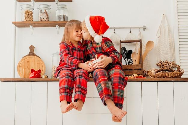 Kinder, die weihnachtsgeschenk halten