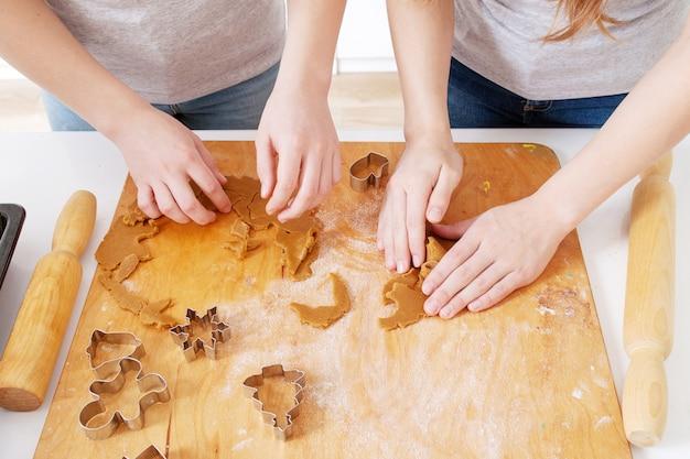 Kinder, die weihnachtslebkuchenplätzchen in der küche am wintertag backen. nahaufnahmekinderhände, die plätzchen unter verwendung der ausstechformen zubereiten. kochen mit kindern für weihnachten zu hause