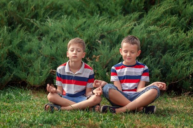 Kinder, die yoga mit geschlossenen augen in der natur praktizieren