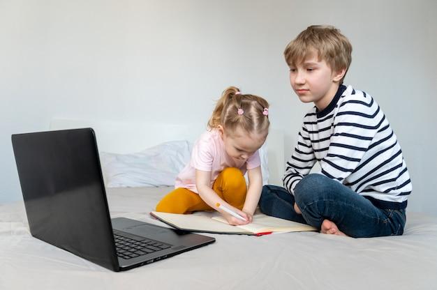 Kinder, die zu hause auf dem bett mit laptop lernen