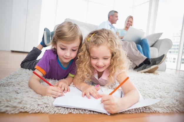 Kinder, die zu hause auf papiere zeichnen