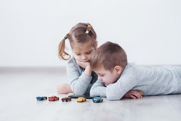 Kinder, die zu hause digitale geräte verwenden. bruder und schwester im schlafanzug schauen sich zeichentrickfilme an und spielen auf ihrem technologietablett