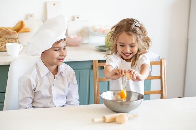 Kinder, die zu hause mit eiern in der küche kochen