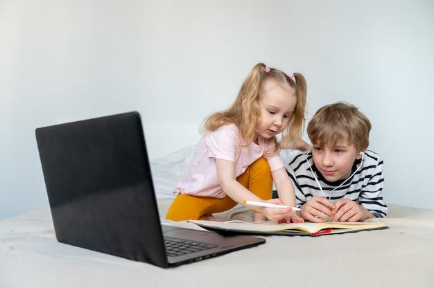 Kinder, die zu hause mit laptop und buch lernen