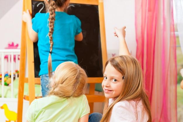 Kinder, die zu hause schule spielen