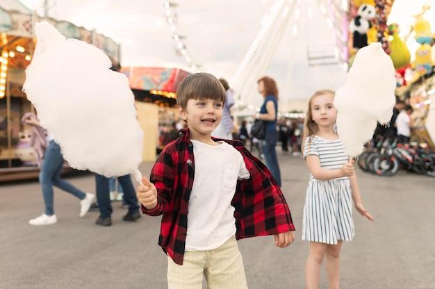 Kinder, die zuckerwatte genießen