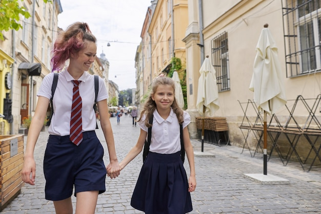 Kinder, die zur schule gehen, zwei mädchenschwestern, teenager und grundschüler mit rucksäcken, die zusammen gehen und hände halten