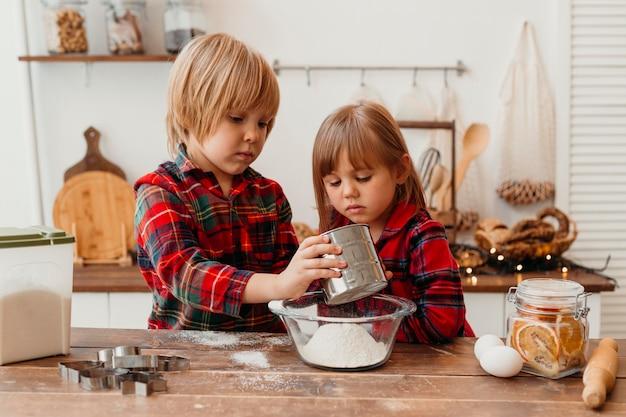 Kinder, die zusammen am weihnachtstag kochen