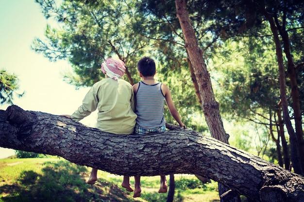 Kinder, die zusammen auf baum sitzen